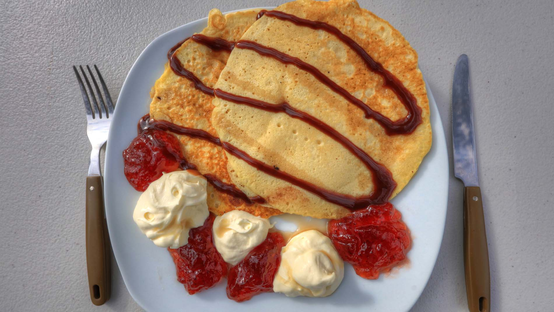 Pancakes, strawberry and cream on a plate