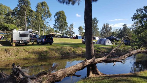 A creek shot with camping grounds behind