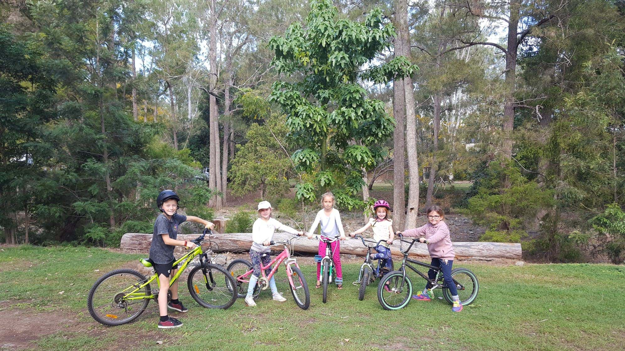 Five young kids on their bikes