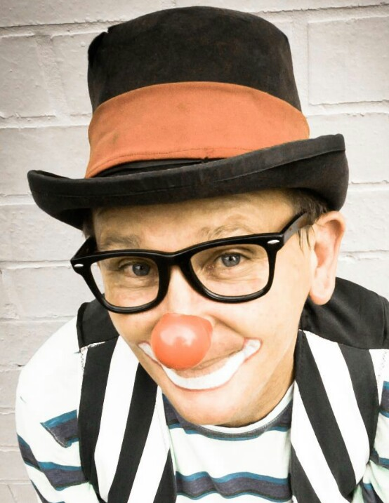 Clown made up with top hat & striped shirt.